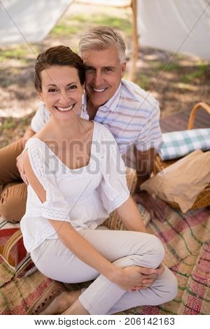 Portrait of happy couple sitting in cottage during safari vacation