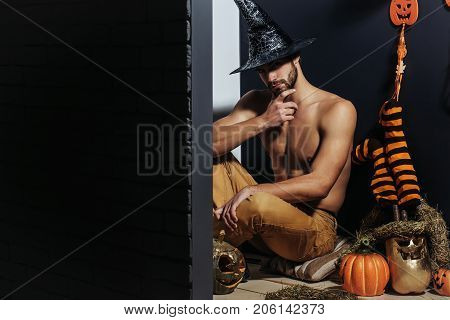 Halloween spirit and supernatural concept. Macho in witch hat and bared torso sitting on floor. Man and pumpkins stockings ghost on black wall. Evil spell and magic. Autumn holidays copy space poster
