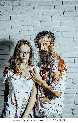 Halloween man hugging woman in eyeglasses on white brick wall. Couple in love bleeding with red blood. Girl and hipster in bloody torn clothes. Halloween holiday celebration concept