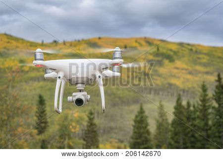 Kenosha Pass, CO, USA - September 14, 2017:  Radio controlled DJI Phantom 4 Pro quadcopter drone is flying with a camera in Rocky Mountains with fall colors.