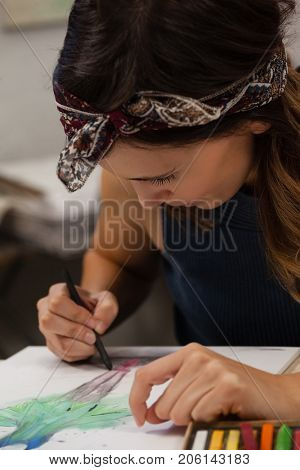 Attentive woman drawing on book in drawing class