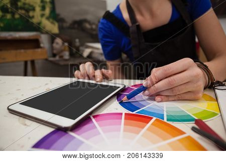 Mid section of woman matching color with color swatch at table