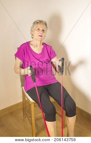 Rehabilitation exercises with elastic resistance rubber for older woman with cerebral stroke poster
