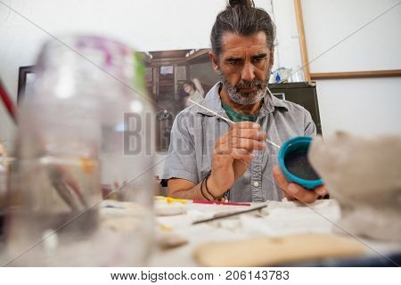 Attentive man painting bowl in class