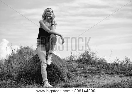 young pretty woman with long lush curly blonde hair and sexy body sitting on stone in in field with grass and blue cloudy sky outdoor on natural background