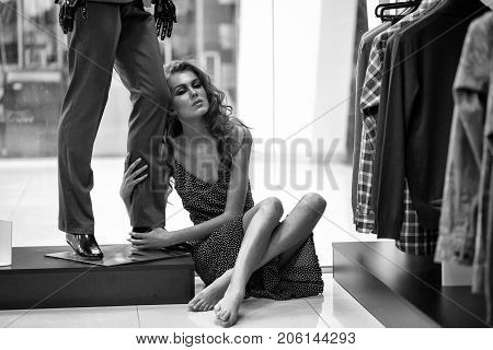 Pretty Girl Sits On Floor At Male Mannequin In Shop
