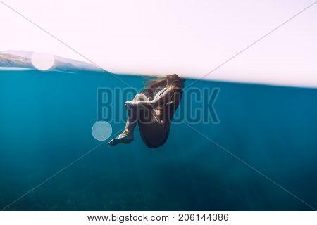Woman floating in blue ocean. Underwater view