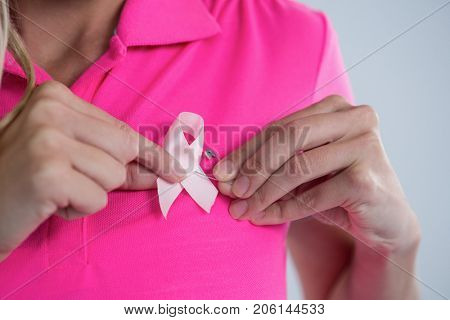 Mid section of woman attaching pink breast cancer awareness ribbon