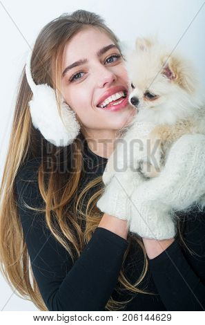 Dog in hand of woman on white background. Girl with happy face in gloves and ears. Woman with small dog of Pomeranian Spitz. New year of dog and winter holiday celebration. Xmas party and vacation.
