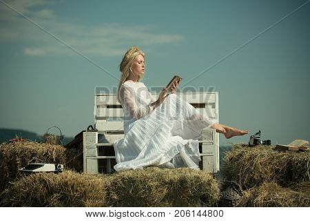 Student with camera and typewriter on hay. Girl in straw wreath and white dress on sunny day. Summer holidays and vacation. Hobby and lifestyle concept. Woman reading book on bench on blue sky.