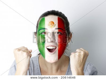 Mexican fan screaming GOAL with hands up and painted flag on her face.