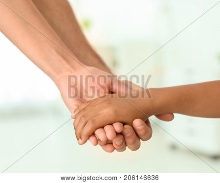 Parents holding hand of small African-American child on light background. Adoption concept