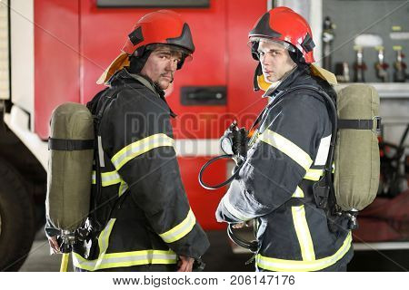 Two firefighters in protective suits and red fire helmet to protect head standing against fire engine, view from back, look around