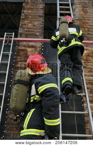 two firefighters in equipment and helmets on test site, one of them climbs ladder