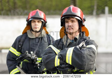 two heroic fireman in protective suit and red helmet, man in foreground crossed his arms over his chest