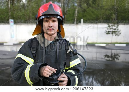 Portrait of fireman wearing fire fighter turnouts and red fire helmet to protect head