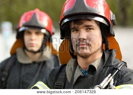 Portrait of two heroic fireman in protective suit and red helmet, closeup