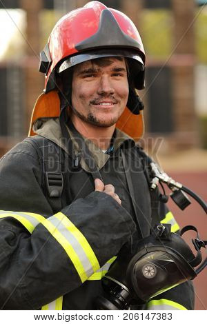 Portrait of fireman wearing fire fighter turnouts, red helmet and breathing apparatus, closeup