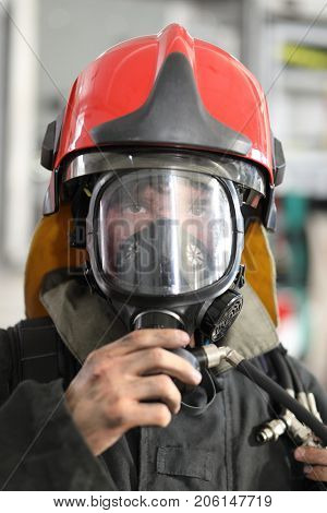 fireman wearing fire fighter turnouts and red helmet with breathing apparatus on background of fire truck, closeup