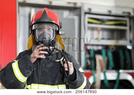 fireman wearing fire fighter turnouts and red helmet with breathing apparatus on background of fire truck
