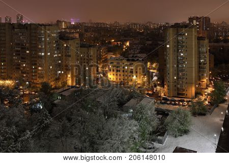 city landscape from window of multi-storey building, snow in spring, evening