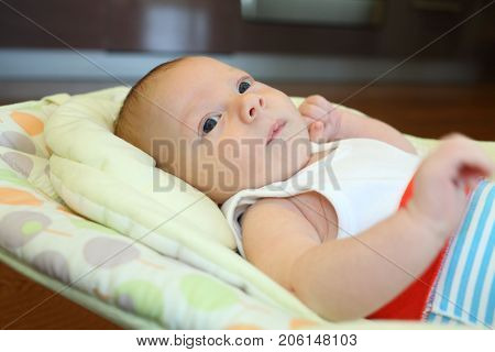 Newborn naked baby boy lying in cradle, look throw, close-up