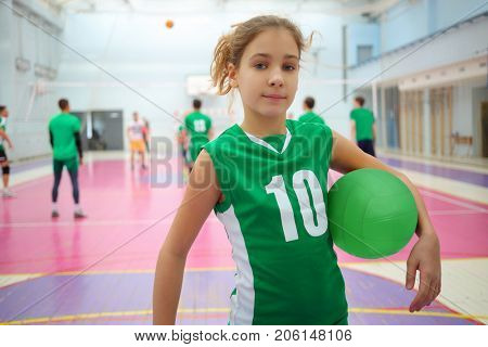 Pretty girl in green stands with ball in gym during volleyball game, playing people out of focus