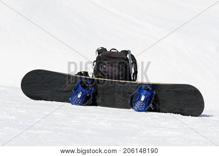 Snowboard And Backpack On Ski Slope
