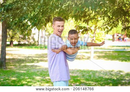 Young father playing with adopted African American boy outdoors