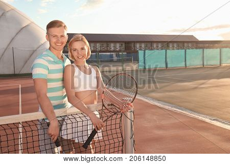 Young couple standing on tennis court