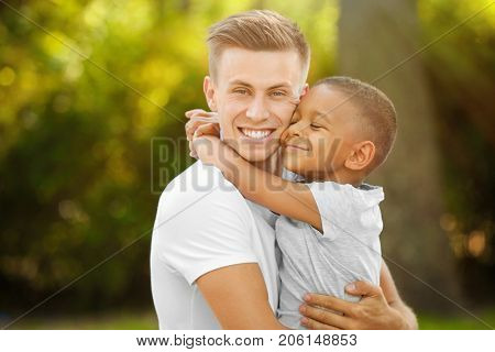 Young man with adopted African American boy outdoors