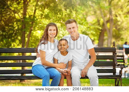 Young family with adopted African American boy sitting on bench in park