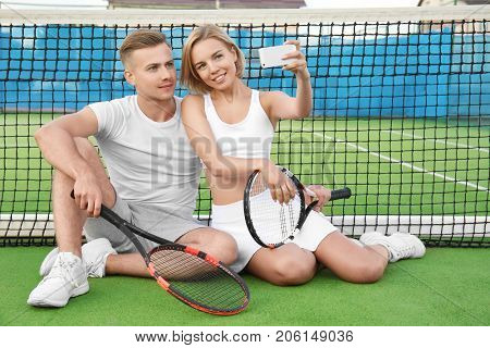 Young couple with tennis rackets taking selfie on court
