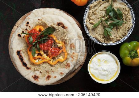Pita bread, turkish or lebanese flatbread with hummus and pepper relish
