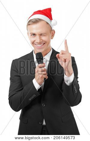 Young presenter in Santa hat with microphone on white background