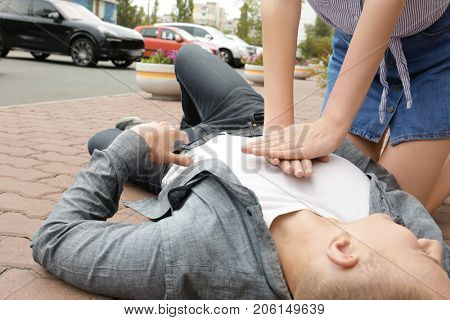 Woman giving first aid to young man with heart attack on street