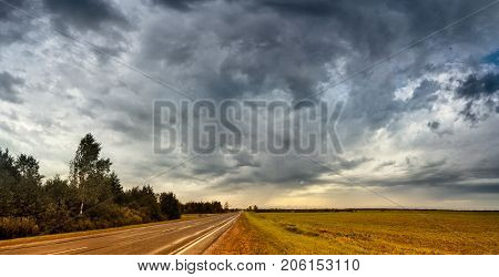 Empty road in cloudy rainy autumn day panorama. Wet road landscape under cloudy sky.