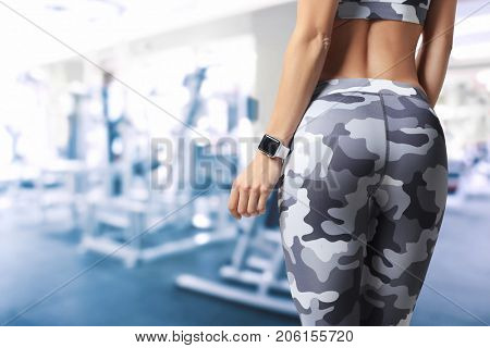 Sporty young woman with fitness tracker in gym