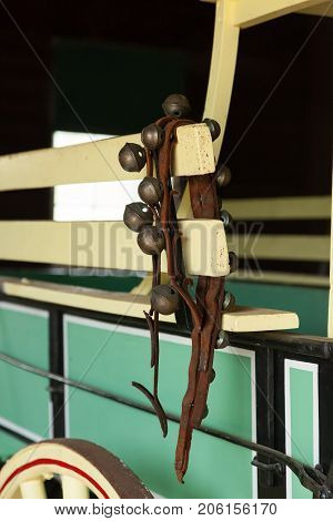 Jingle bells on a leather strap hang over the side of an old wooden wagon.