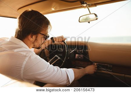 Photo from car of Young bearded man in sunglasses turning on stereo system while sitting in a retro car with hand on a steering wheel