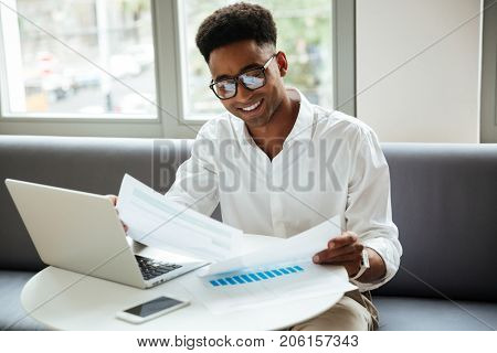 Picture of happy young african man sitting coworking by laptop computer holding documents. Looking aside.