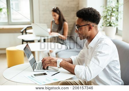 Picture of concentrated young african man sitting coworking by laptop computer. Looking aside.