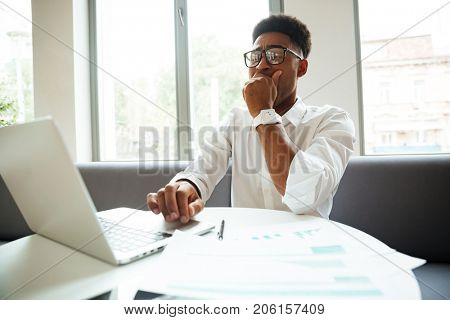 Image of yawning young african man sitting coworking by laptop computer. Looking aside.