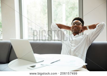 Photo of cheerful young african man sitting coworking by laptop computer. Looking aside.