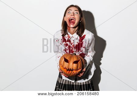 Insane smiling zombie woman covered in blood stains holding a halloween pumpkin isolated over white background