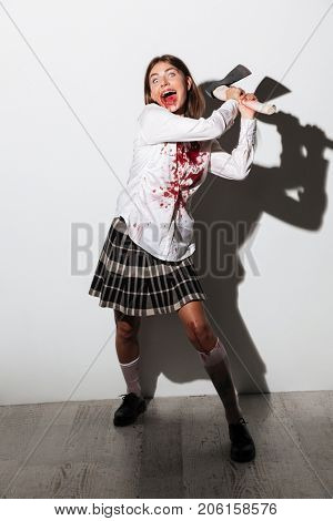 Full length of a smiling mad zombie woman holding an axe and ready to attack isolated over white background