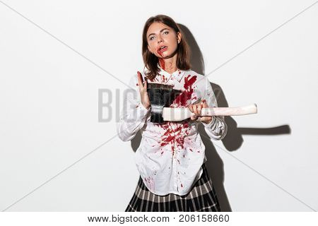 Wicked undead zombie woman holding an axe and looking at camera isolated over white background