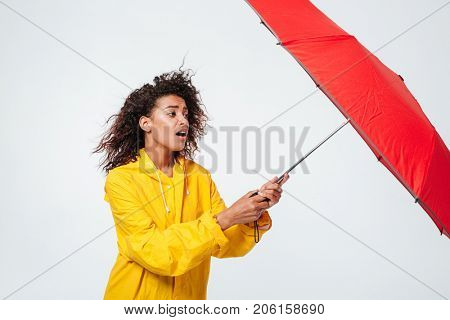 Side view of confused african woman in raincoat holding umbrella over white background