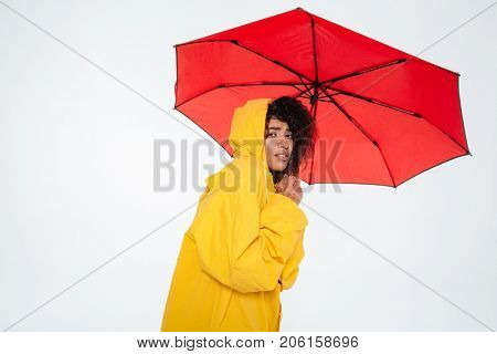 Young african woman in raincoat hiding behind umbrella and looking at the camera over white background