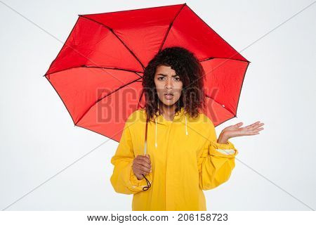 Confused young african woman in raincoat hiding under umbrella and looking at the camera over white background
